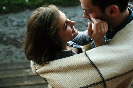 parejas: Pareja joven en el amor envuelto en tela escocesa de pie y mirando el uno al otro Foto de archivo