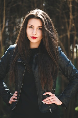 sexy babe: young beautiful girl posing in a black leather jacket in the park Stock Photo
