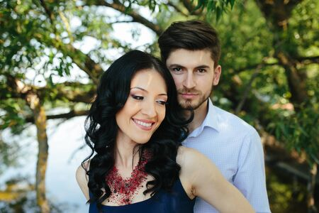 woman happy: portrait of a young man embracing his girlfriend from behind Stock Photo
