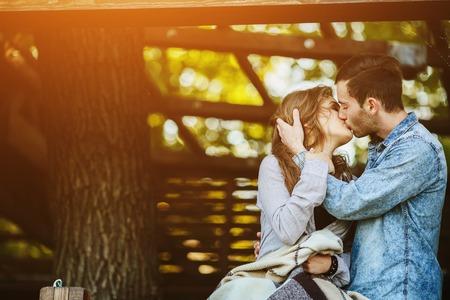 Coppia giovane innamorato avvolta in piedi plaid e baciare
