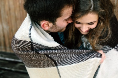 persona sentada: Joven pareja de enamorados envuelta en sesi�n de tela escocesa y divertirse
