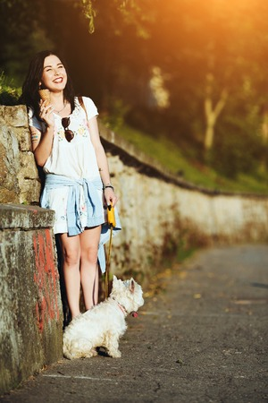 ice cream stand: Girl with ice cream and dog against the wall