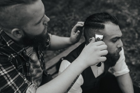 barber background: barber shaves a bearded man in vintage atmosphere Stock Photo