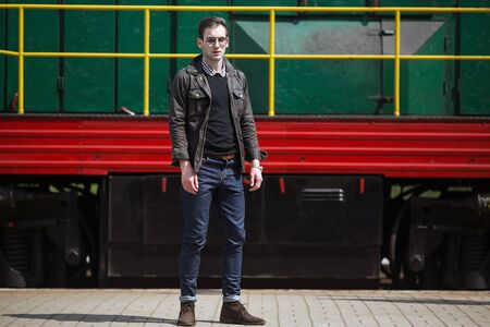 british ethnicity: A man dressed in jeans on the background of the train and the st Stock Photo