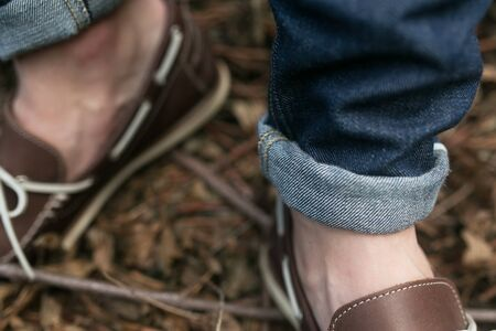 british ethnicity: Feet of the man in the authentic boots and  selvedge jeans,on the background of branches Stock Photo