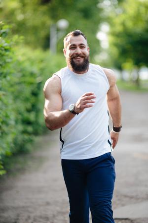 hombre con barba: bearded man running a cross in the park at green fence Foto de archivo