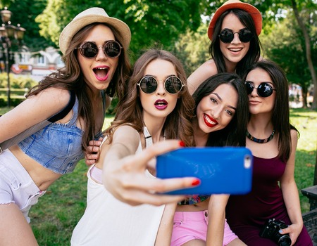 having: five beautiful young girls make selfie in the park