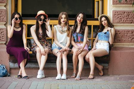 Five beautiful young girls relaxing in the city