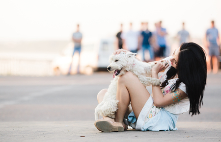 city people: beautiful girl sitting on the street and playing with her dog Stock Photo