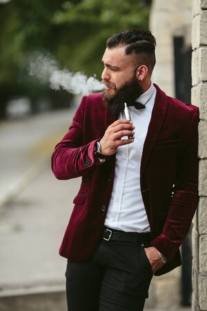 male beauty: a rich man in a jacket near his house