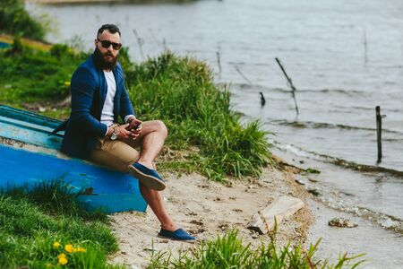 male beauty: American Bearded Man looks on the river bank in a blue jacket Stock Photo