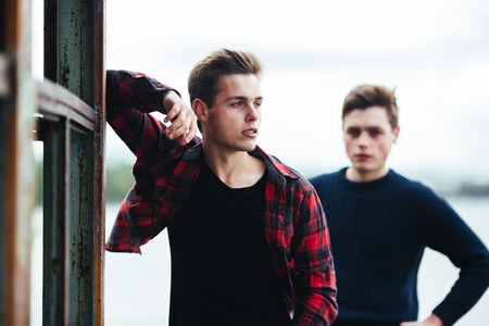 only men: two young guys stand in an abandoned building on the lake