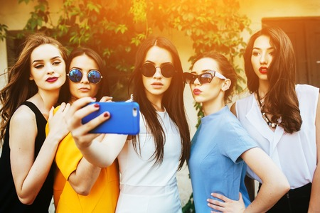 cinco hermosas chicas jóvenes hacen selfie en la calle cerca de la casa Foto de archivo