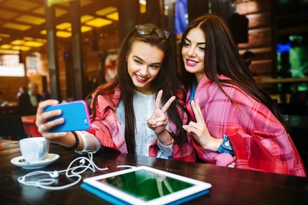 Two young and beautiful girl sitting at the table and doing selfie in the cafe Banque d'images