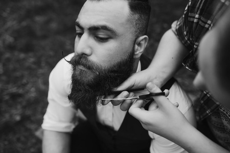 barber shaves a bearded man in vintage atmosphere Archivio Fotografico