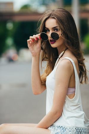 beautiful girl in sunglasses sitting on the asphalt
