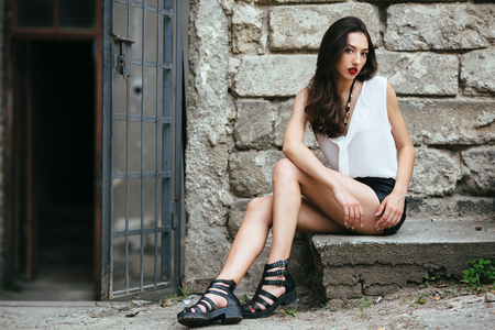 sensual girl: young and beautiful girl sitting at the door on a stone slab