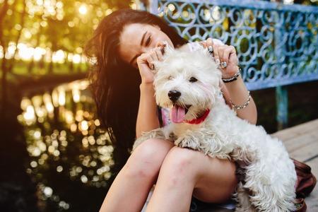 jovenes felices: ni�a jugando con un perro en la orilla del r�o cerca del puente Foto de archivo