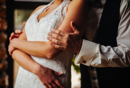 The hand of the groom gently embraces the bride