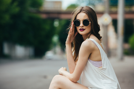 fashion: beautiful girl in sunglasses sitting on the asphalt