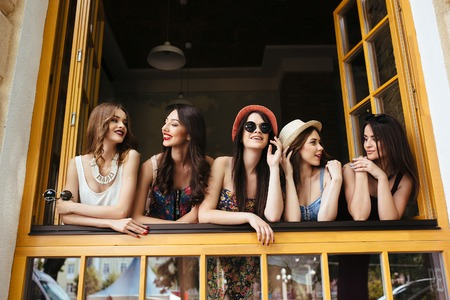 girl in shorts: five beautiful young girls look out from the window Stock Photo