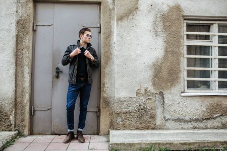 A man dressed in jeans on the background of doors