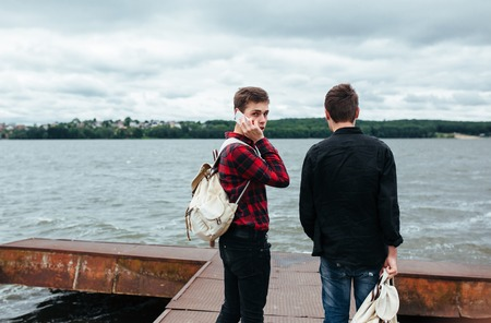 behind scenes: two young guys stand on the pier and one of them turned his head Stock Photo
