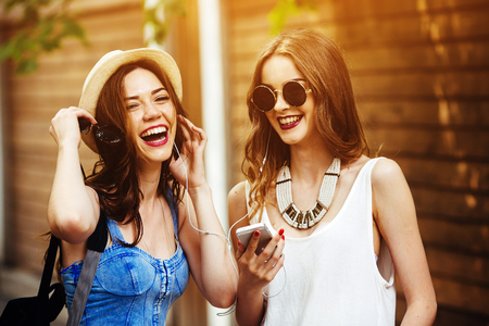 teens: Two young beautiful girls are walking through the city and listen to music Stock Photo