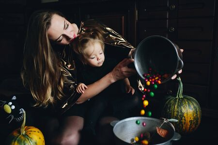 playing with spoon: mother and daughter playing together at home on Halloween Stock Photo