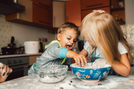 work from home: Kids is playing with flour in the kitchen