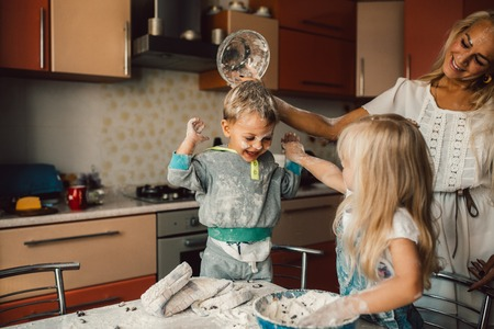 life at home: mother and children playing on kitchen with flour