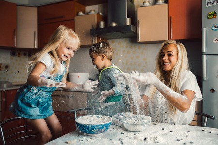 woman sitting on floor: mother and children playing on kitchen with flour