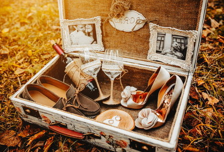 retro lady: suitcase with different wedding accessories in the background leaves Stock Photo