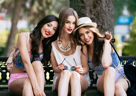 Tres chicas jóvenes hermosas que presentan contra el telón de fondo del parque