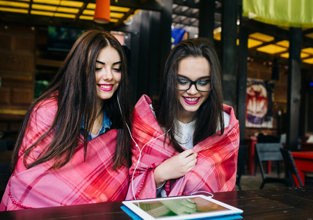 joy pad: Two young and beautiful girl sitting at the table watching something on a tablet Stock Photo