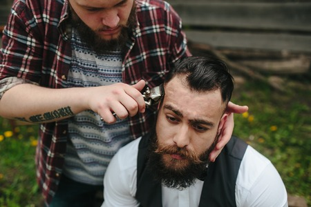 barbero: barbero afeita a un hombre barbudo en la atmósfera de la vendimia Foto de archivo