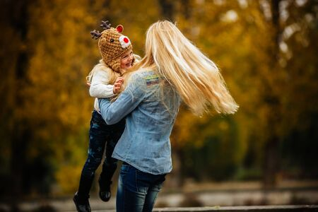 is real: mother and daughter having fun in autumn park
