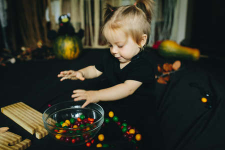 playing with spoon: little girl playing in a witch on Halloween