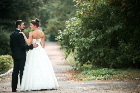 forest park: Beautiful wedding couple in each others arms in the park Stock Photo