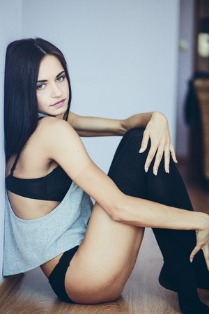 naked girl black hair: half-naked beautiful young model sitting on the floor bent legs