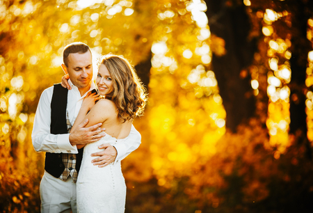 beautiful couple posing on a background autumn forest