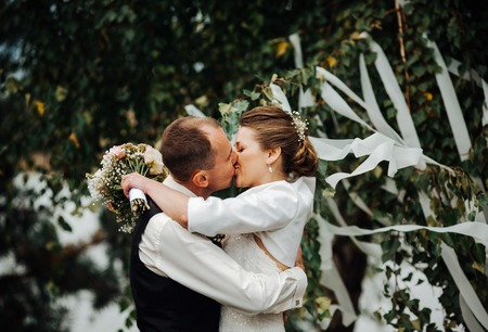 hombres besandose: beautiful bride kisses the groom at a wedding ceremony