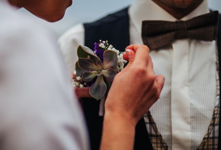 boutonniere: young woman adjusting boutonniere on groom suit
