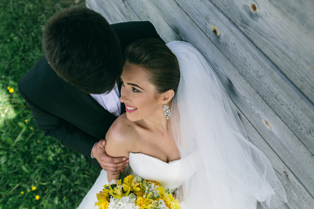 woman in dress: beautiful young wedding couple stands near the old wooden house. Photo from the top