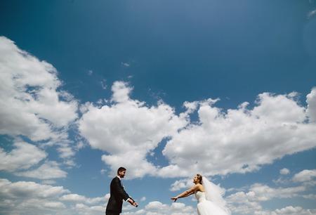 Beautiful wedding couple on the background of blue sky
