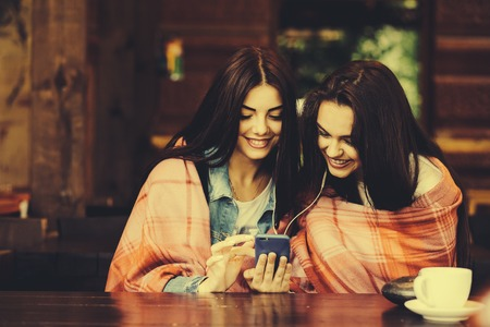 listening: Two young and beautiful girl sitting at the table listening to music with a smartphone Stock Photo