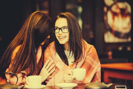 chismes: Dos chicas j�venes y hermosas que chismean en la terraza con una taza de caf�