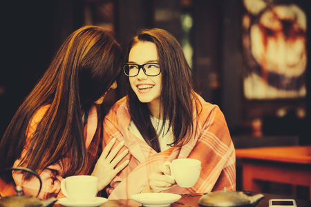 white girl: Two young and beautiful girls gossiping on the terrace with a cup of coffee