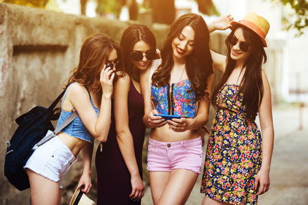 trendy: four young beautiful girls on the street looking at the photos on a smartphone