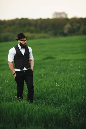 three day beard: Man with a beard and sunglasses in the green field